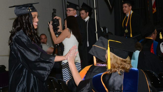 Jennifer Innerarity (right), assistant professor of Criminal Justice, congratulates Samantha Thomas (left) after Thomas received her bachelor of science degree in criminal justice from LSUA during commencement ceremonies held Thursday at the Riverfront Center in downtown Alexandria.