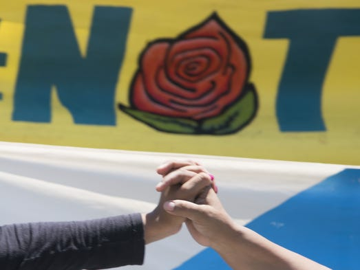 Dos manos inmigrantes en unión durante una protesta