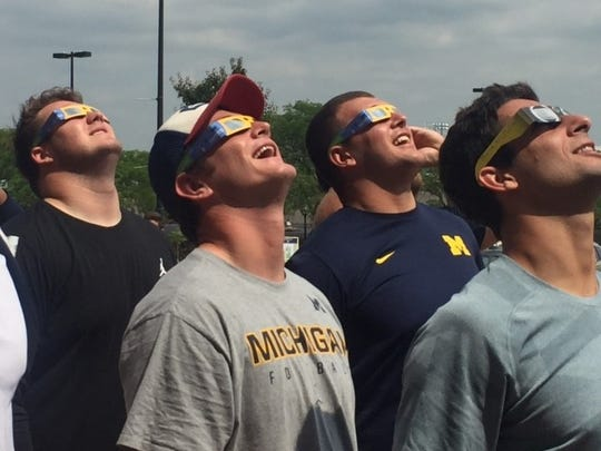 Michigan football players, including Peter Bush (hat), Ben Bredeson (rear) and Jack Wangler (front) watch the eclipse.