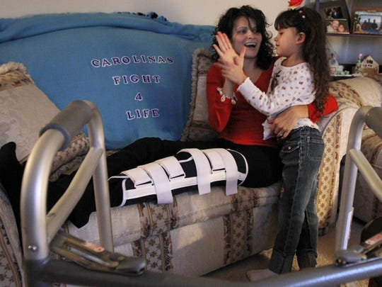 Carolina DeHond gives her daughter Mikayla Sabel, 5, a high-five as they sit together in their home in Penfield Monday, Nov. 22, 2010.