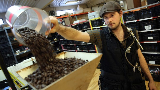 Benjamin Lisser of Just Coffee Cooperative in Madison, Wis., prepares in 2015 to grind coffee beans. The glass tube on his vest collects air in his breathing zone to test for diacetyl and 2,3-pentanedione, two chemical compounds known to damage lung capacity.