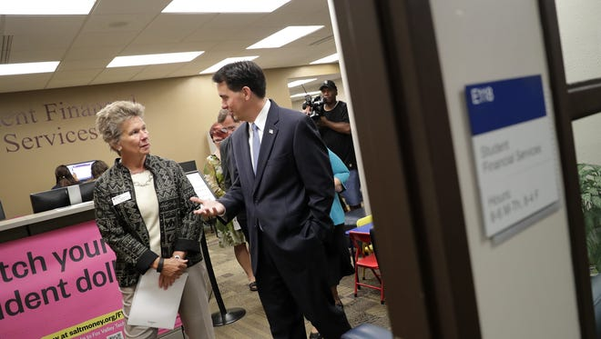 Patti Jorgensen, vice president for student and community development at Fox Valley Technical College, leads Gov. Scott Walker on a tour Tuesday through Student Financial Services at FVTC in Grand Chute.