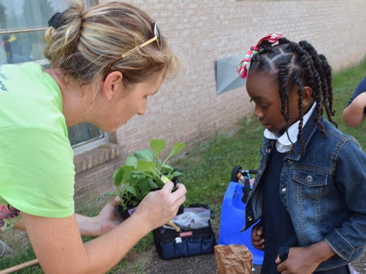 ANI Mabel Brasher Cindy Baker, Good Food community garden manager, asks Mabel Brasher fifth-grader Layla Gray what kind of vegetable plant she is holding. Baker told Layla that it was cabbage that was going to be planted in the school's Good Food garden. -