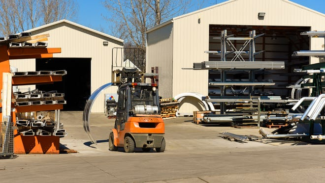 A worker moves parts around Thursday, March 10, at the Polar Tank Trailer manufacturing facility in Holdingford.