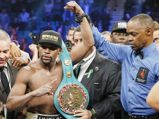 Floyd Mayweather Jr., celebrates his victory over Manny Pacquiao, from the Philippines, with the champion's belt following their welterweight title fight on Saturday, May 2, 2015 in Las Vegas. At right is referee Kenny Bayless. (AP Photo/John Locher)