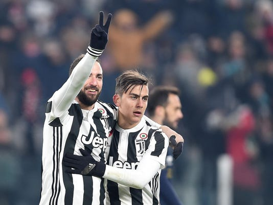 Juventus' Gonzalo Higuain, left, celebrates with his teammate Paulo Dybala after scoring his side's second goal during an Italian Cup round of 16 soccer match between Juventus and Genoa, at Turin's Allians Stadium, Wednesday, Dec. 20, 2017. (Alessandro di Marco/ANSA via AP)