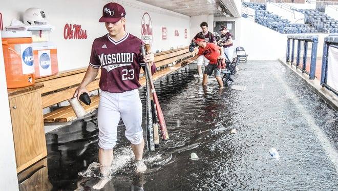 Missouri State outfielder Jack Duffy (23) carries bats out of a flooded first base dugout before the start of the game against Tennessee Tech for the NCAA Oxford Regional, in Oxford, Miss. on Friday, June 1, 2018. (Bruce Newman, Oxford Eagle via AP)
