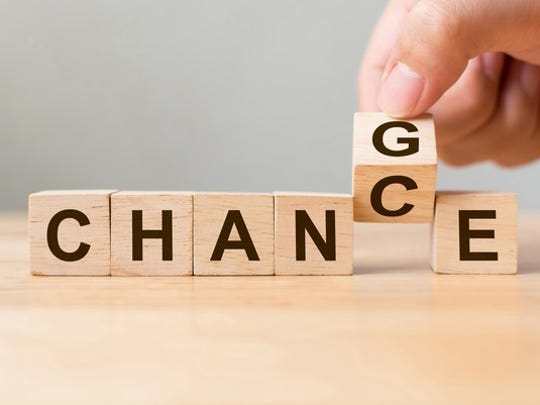 Letters on wooden blocks spell out the word Change, as a hand turns the G over to a C to spell Chance instead.