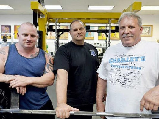 From left, trainer and world-record powerlifter Vincent Cook, Keith Lightner and gym owner Mark Chaillet stand for a portrait Friday, July 31, 2015, at Chaillet's Private Fitness in Manchester Township. Lightner, a Spring Garden Township Police patrol officer, recently won gold for weightlifting in the World Police and Fire Games in Fairfax, Va.