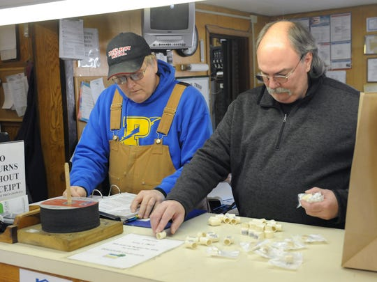 Sheldon Gibbs, left, and Bob Murphy ring up a customer at Higgins Lumber Company in Roseville.