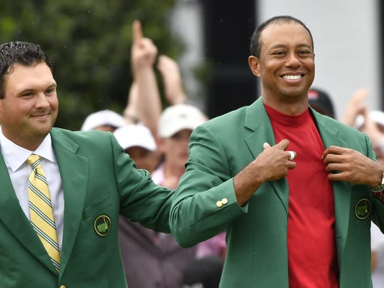 Apr 14, 2019; Augusta, GA, USA; 2018 winner Patrick Reed places the green jacket on 2019 winner Tiger Woods after the final round of The Masters golf tournament at Augusta National Golf Club. Mandatory Credit: Michael Madrid-USA TODAY Sports