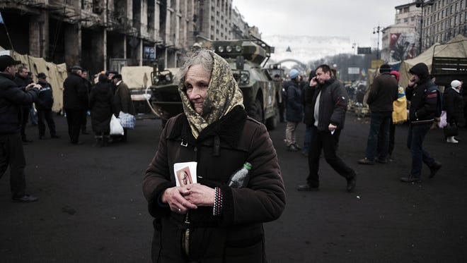 A woman holds a holy icon as she walks on Independence Square in central Kiev on Feb. 25.