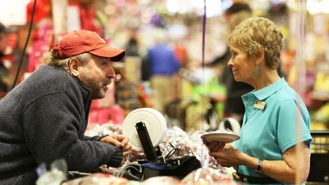Mary Ellen Burris, who on July 4 retired from Wegmans, speaks with a shopper during the grocery chain's 100th anniversay celebration in 2016.
