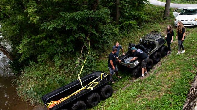 Members of the creek cleanup project prepare to take the new amphibious vehicle into the Conococheague Creek. Dan Rainville- The Evening Sun