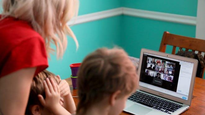 Emily Minelli and her two sons Nico, 3, left, and Tommy, 6, log onto a video conference call in April in Cincinnati's Northside neighborhood. About a dozen of Emily's colleagues rotate teaching their kids a lesson from a range of subjects. On this day, it was Emily's turn.