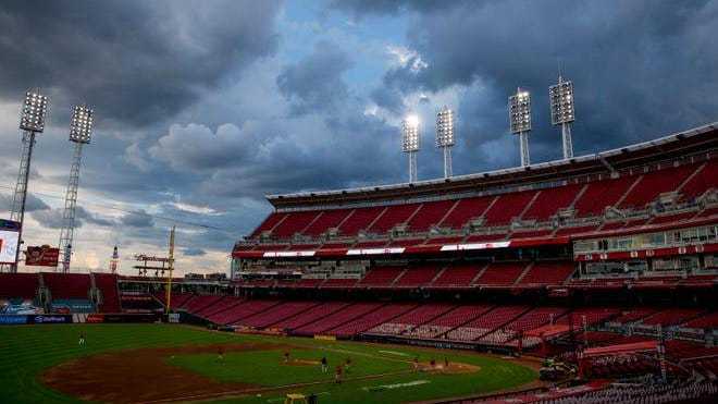 The ground crew at Great American Ball Park in Cincinnati prepare the field for a game between the Cincinnati Reds and the Cleveland Indians on Aug. 3, 2020, that was delayed due to rain.