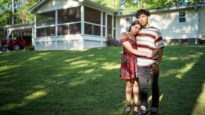 Michael Torres, 18, and his 12-year-old sister Ashley Torres in front of their home in Wake Forest, North Carolina. The family has managed to stay heatlthy, even as Michael Torres works full time with his father.