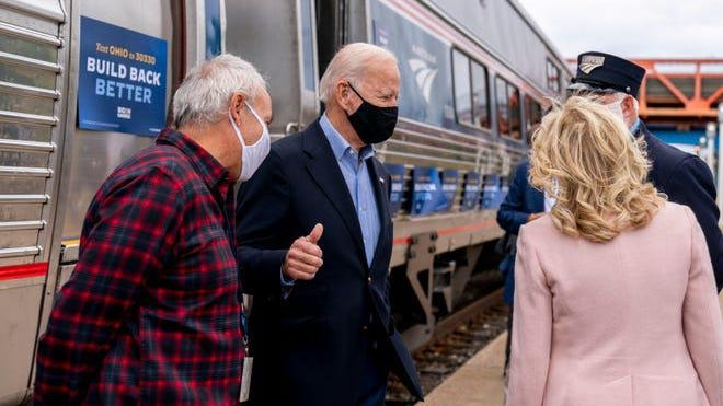 Democratic presidential nominee Joe Biden gives a thumbs up after speaking to his supporters before boarding his train with his wife Jill Biden, right, at Amtrak's Cleveland Lakefront train station on Sept. 30 2020.