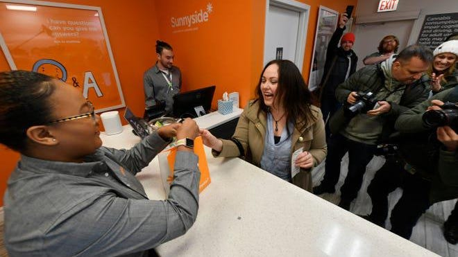 Jackie Ryan, right, of Forest Park, Ill. becomes the first person in Illinois to purchase recreational marijuana on January 1, 2020.