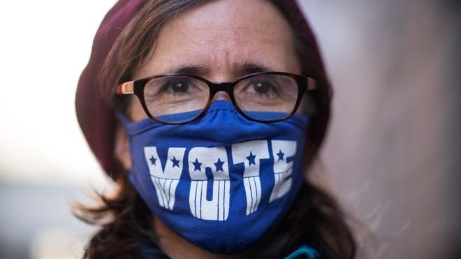 """Cathy Saunders wears a """"VOTE"""" mask while standing in line to cast her ballot in Providence."""