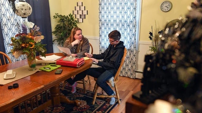 Shawna Diedrich helps her son, Trey Diedrich, student for a math test last fall at their home in Mitchell, South Dakota. Even though the test was on content that Trey said he learned the previous year, he said he did not understand how to do some of the problems.