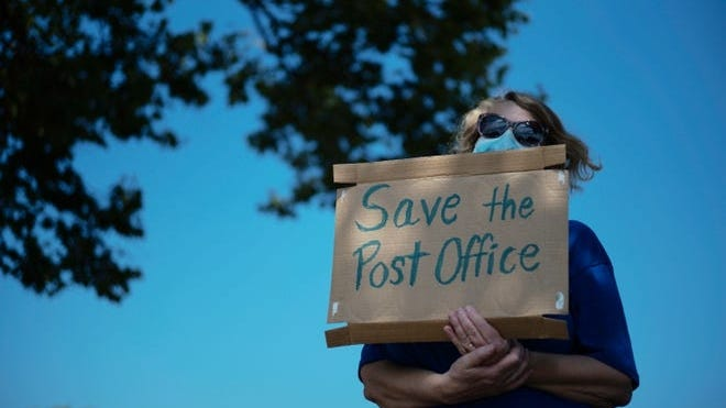 Activist Rebecca Slisher, of Groveport, holds a sign while rallying with others during a Save the Post Office Rally on Aug. 22 in Whitehall, Ohio.