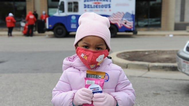 A young child holds free snacks outside an early voting site on Oct. 30, 2020, in Milwaukee.