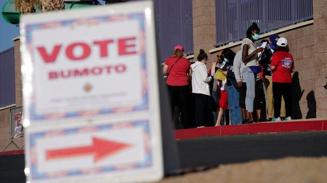 People wait in line to vote at a polling place on Election Day in Las Vegas.