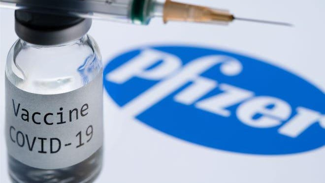 """In this file photo illustration taken on November 23, 2020, shows a syringe and a bottle reading """"Covid-19 Vaccine"""" next to the Pfizer company logo. - An expert committee convened by the US Food and Drug Administration on December 10, 2020, voted heavily in favor of recommending the Pfizer-BioNTech Covid-19 vaccine for emergency use approval."""