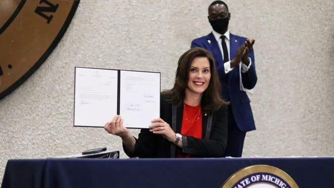 Gov. Gretchen Whitmer signs legislation expanding Michigan's expungement laws during a news conference Monday, Oct. 12, in Detroit.
