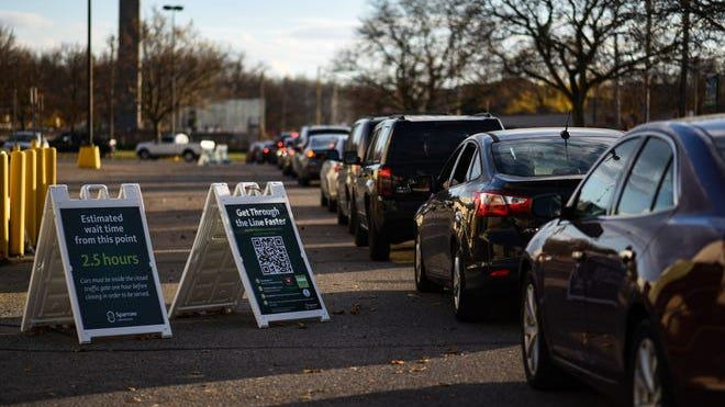 A long line of vehicles lined up at Frandor Shopping Center in line for Sparrow Healthcare's drive thru COVID-19 testing services, pictured Monday, Nov. 9, 2020, in Lansing.