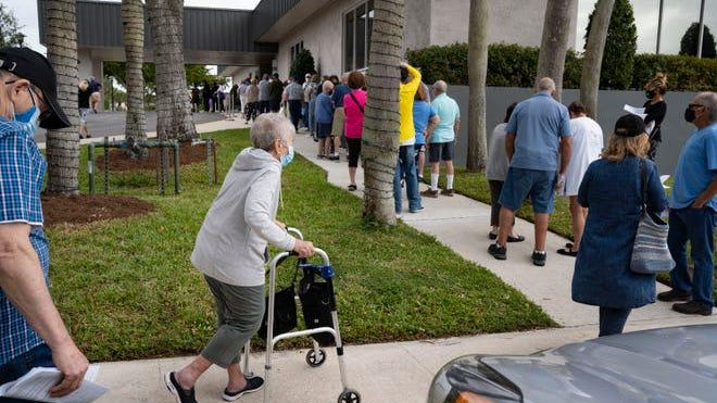 Seniors stand in line to make an appointment to receive the Moderna COVID-19 vaccine outside the King's Point clubhouse in Delray Beach,  Fla., on Dec. 30, 2020.