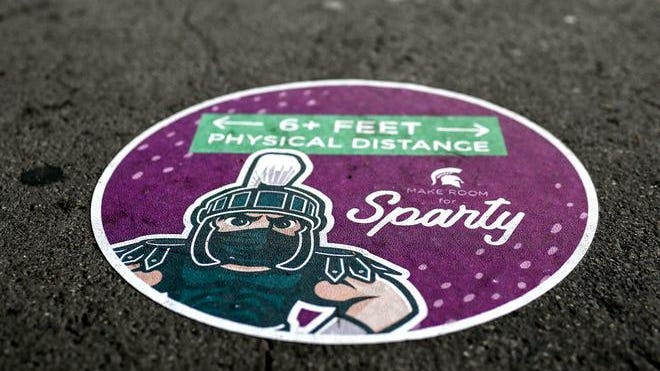 A sticker on the ground reminds people to maintain social distance at the COVID-19 testing site at Spartan Stadium on Tuesday, Nov. 24, 2020, in East Lansing.