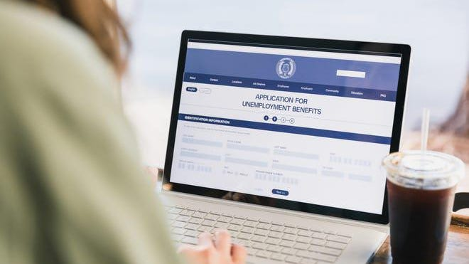 An over the shoulder photo of an unrecognizable woman applying for unemployment benefits.  She is using the government website.