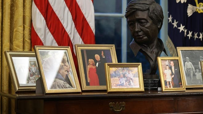 A bust with Cesar Chavez, the labor leader and civil rights activist, is nestled among an array of framed family photos displayed on a desk behind the Resolute Desk in the Oval Office.