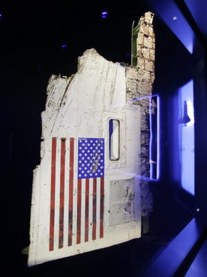 """A side body panel of the space shuttle Challenger is displayed in the """"Forever Remembered"""" exhibit at the Kennedy Space Center Visitor Complex in Cape Canaveral, Fla."""