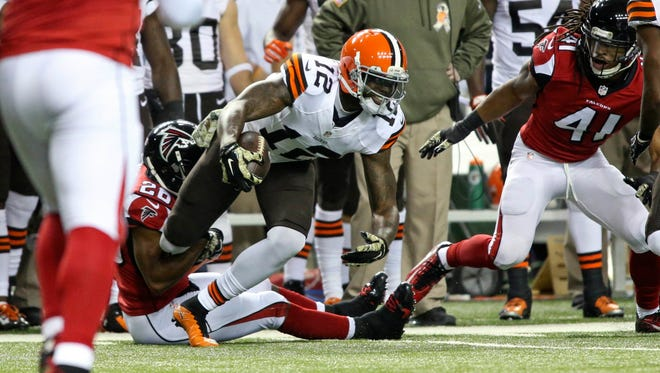 Cleveland Browns wide receiver Josh Gordon tries to get out of the tackle of Atlanta Falcons cornerback Josh Wilson during the first quarter of their game at the Georgia Dome in 2014.