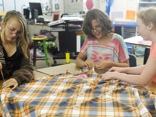 Silverland Middle School students (from left) seventh-grader Adrianna Brown, seventh-grader Karmyn Brown and eighth-grader Gwyneth Crowe tag-team a quilt. They said by working together they can make one in less than half an hour.