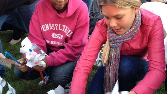 """(From left) Seventh graders Zoey Nwamgale and Emma Hahn work together to set up some of the """"pinwheels for peace"""" on the grounds of East Middle School on Friday morning."""