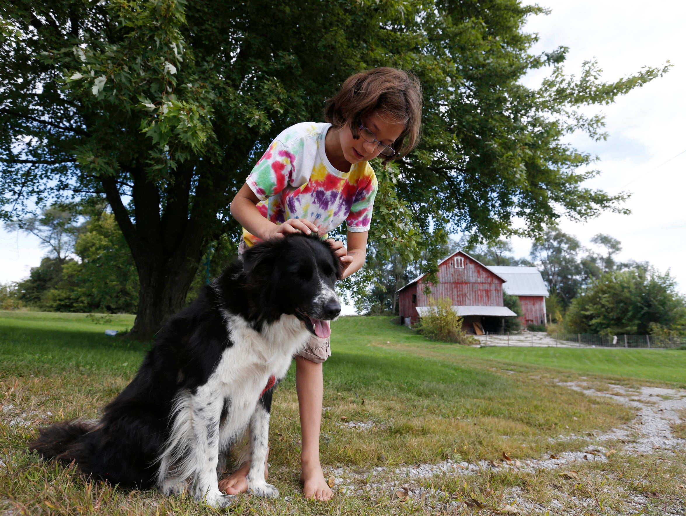 Kali Miller, 9, plays with her dog, Lady, as she talks