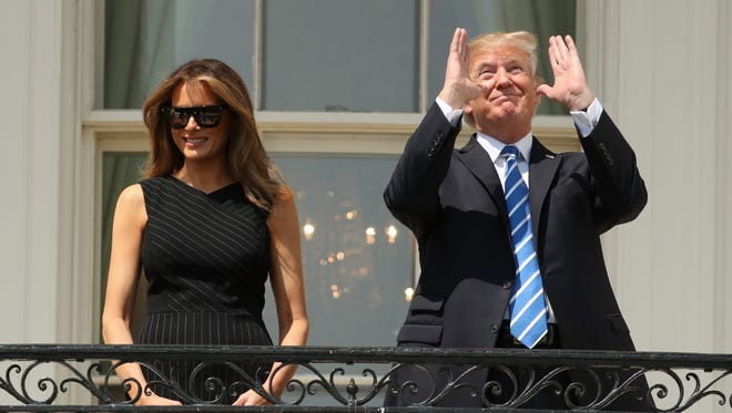 President Trump, accompanied by first lady Melania Trump, view the solar eclipse at the White House on Aug. 21, 2017.