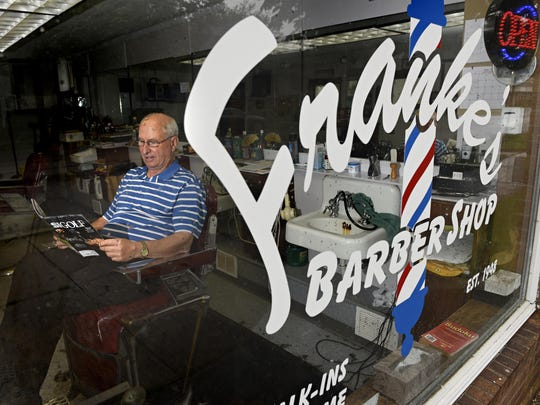 Barber Joe Rieder, owner of Franke's Barber Shop on St. Germain Street, waits for a customer as the rain falls Wednesday. Reider, an avid golfer, spends his open time reading golf magazines and listening to the radio.
