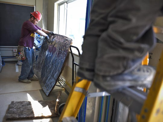 Logan Reid, Diamond Energy Systems Inc., insulates ductwork in a classroom as construction continues Wednesday at North Junior High School.