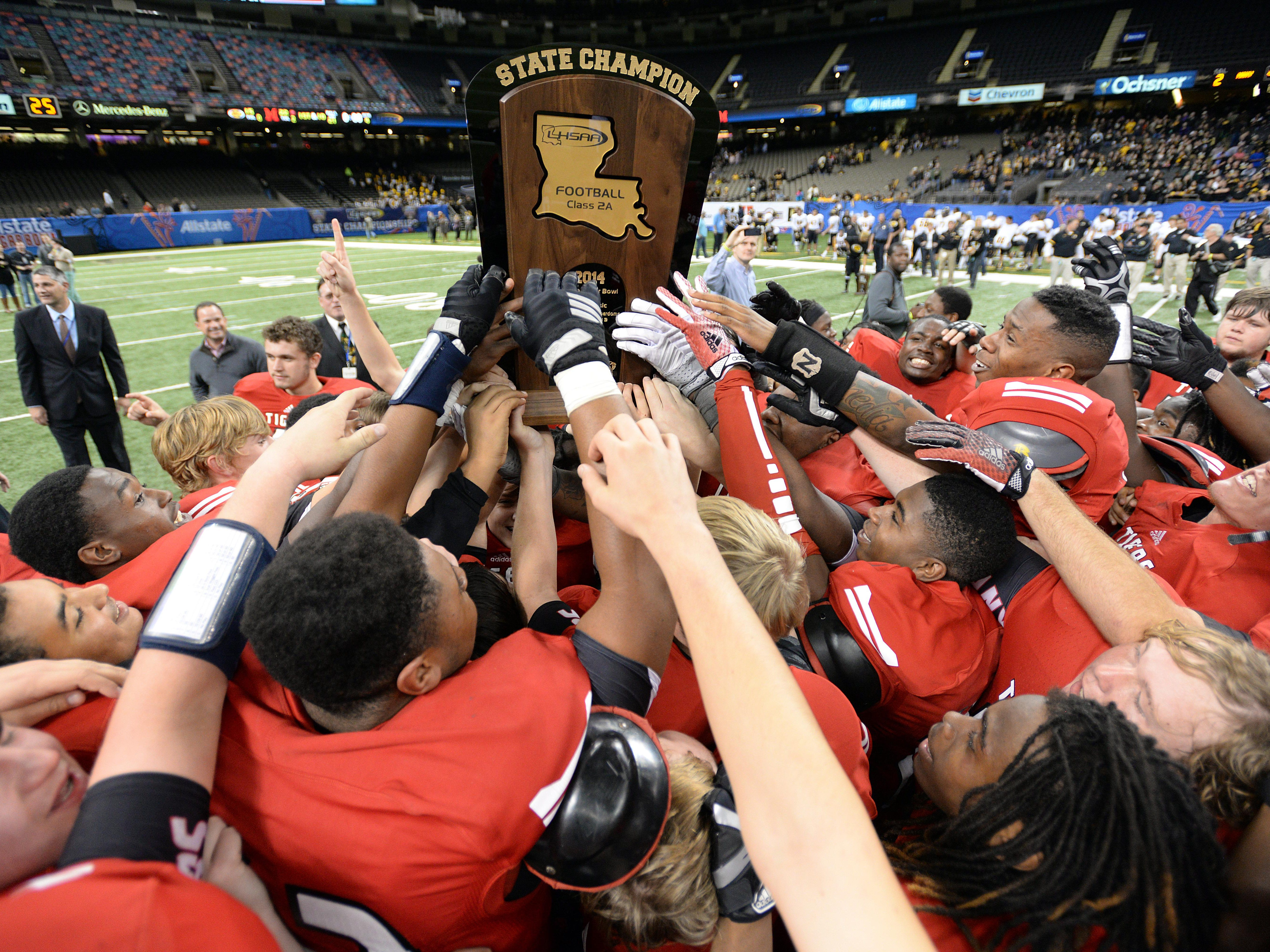 The Many Tigers celebrate after defeating the Kinder Yellow Jackets 22-15 in the 2014 LHSAA Class 2A championship game with Kinder in the Mercedes-Benz Superdome.
