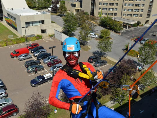 Eric Flegenheimer, chairman of the Flynn Center's Over the Edge fundraising event, rappels off the ninth floor of the Marriott Burlingotn Harbor hotel dressed as Spider-Man on Friday.