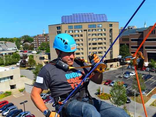 Burlington Police Chief Brandon del Pozo begins his decent off of the ninth floor of the Marriott Courtyard Burlington Harbor in Burlington for the Over the Edge fundraiser for the Flynn Center on Friday.