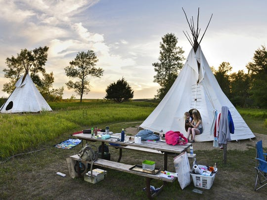 Andrea Falle, left, Melissa Bownik, in back, and Kate Schroeder look over photos July 21 as they camp in one of Blue Mounds State Park's two teepee camping sites.