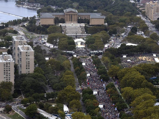People listen to Pope Francis during a Mass on the Benjamin Franklin Parkway on Sunday.