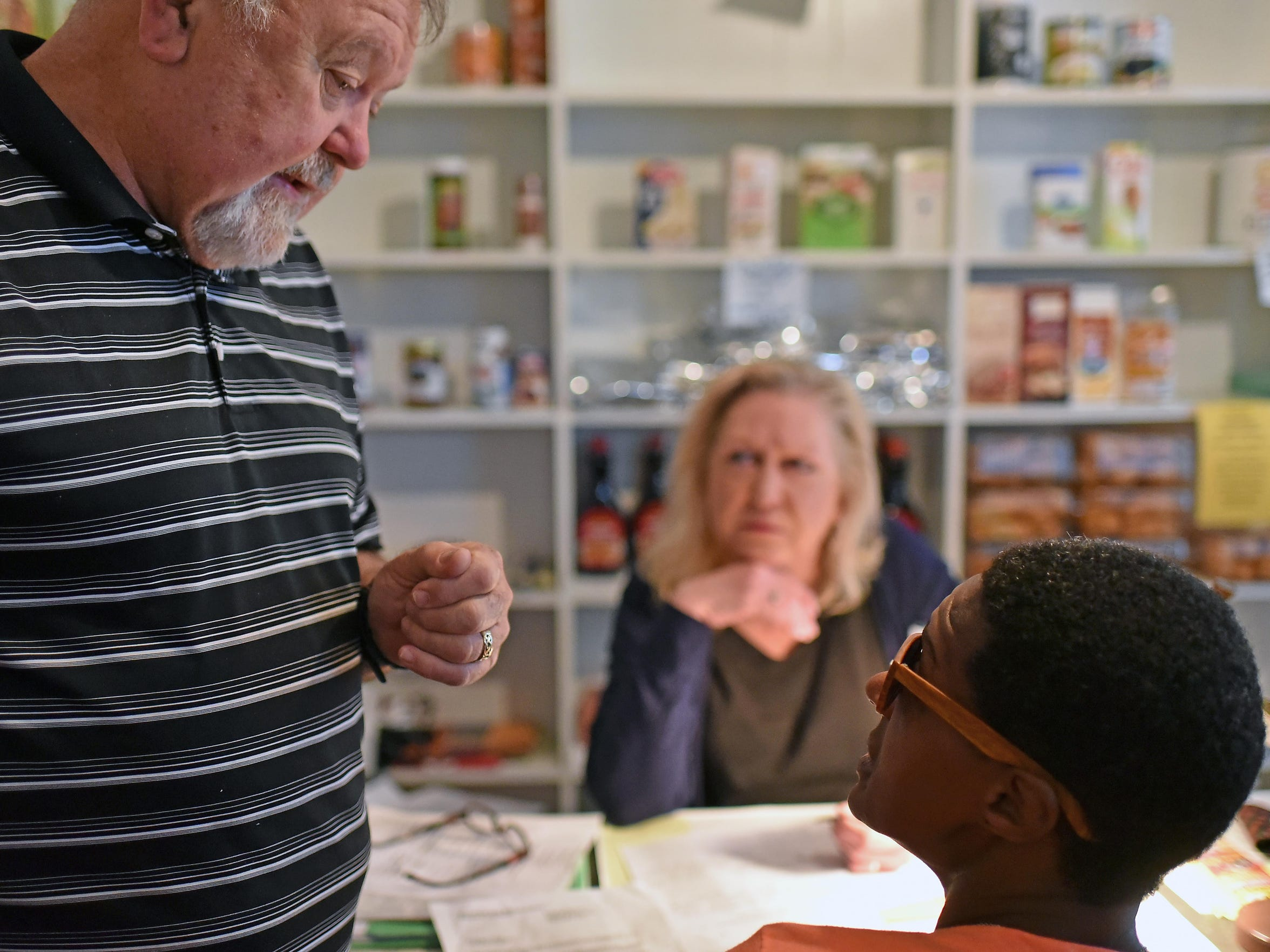 Chuck Brett, executive director of Help & Hope Ministries in Millville, talks with Parmella Wise as she registers to receive food.