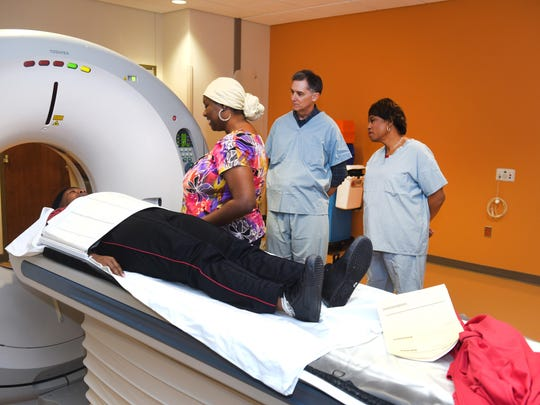 Rep. Brenda Lawrence, D-Mich, right, and Rep. French Hill, R-Ark, wear hospital scrubs as they watch DMC Cat Scan Tech Shasca Barrett-Stevens prepare patient Bridget Burton-Goodman for a scan at DMC Sinai-Grace Hospital.